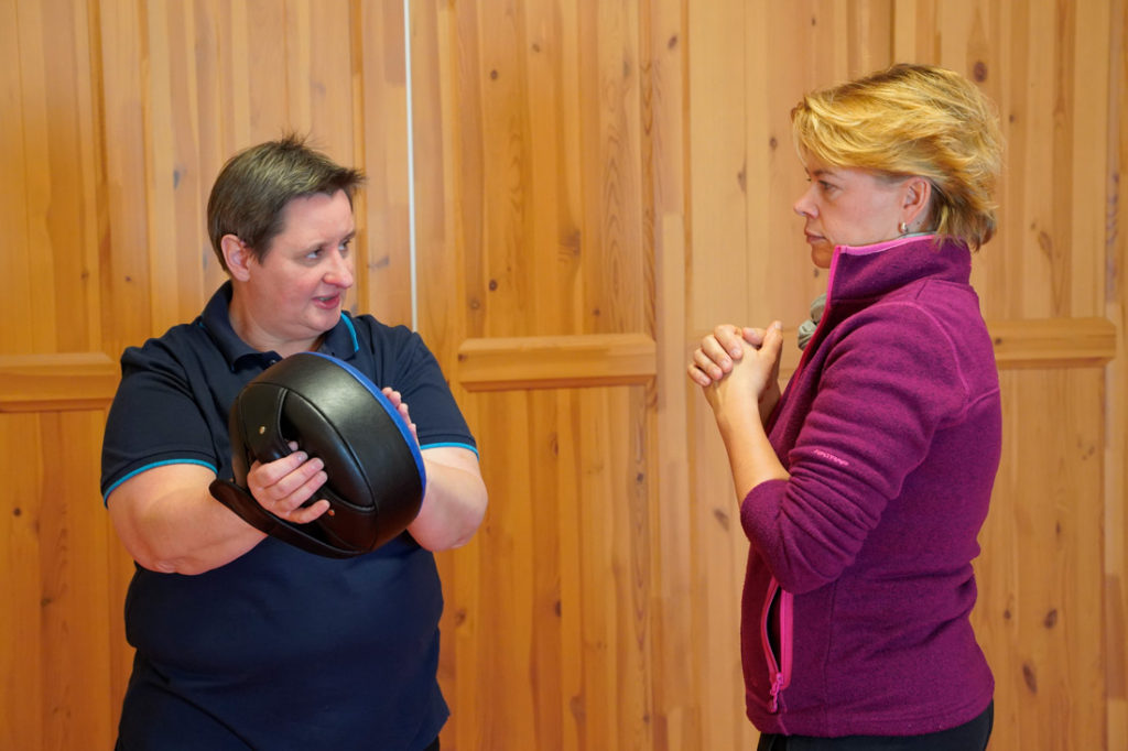 Kathrin Bein, WenDo-Trainerin uas Dresden erklärt einer Kursteilnehmerin wie sie den Schlag auf ein Schlagpolster ausführen soll.